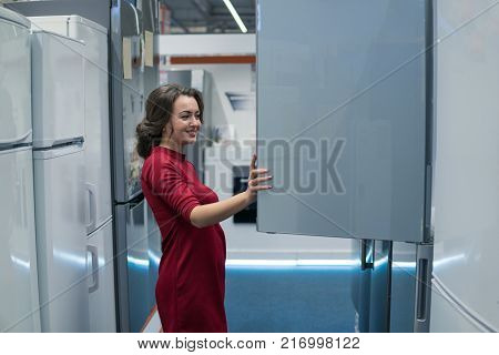 Smart modern female housewife customer choosing large fridges in domestic appliances section. She looks happy
