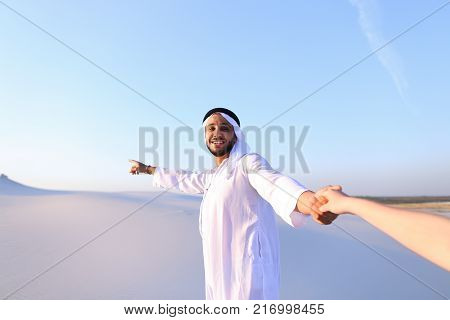 Cheerful Arab male with kindly smile on face leads woman's arm from camera and shows desert landscapes, conducts outing in middle of bottomless sandy desert with white clean sand against blue sky in open air. Swarthy, handsome Muslim with short dark hair