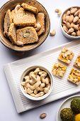Indian sweet food group photo. Dry fruit laddu, kaju katli or kaju burfi, gajak or til papdi, rasmalai or Rasmalai, gulab jamun poster