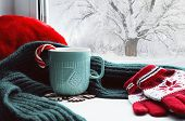 Winter background - cup with candy cane scarf and gloves on windowsill and winter scene outdoors. Winter still life, concept of spending winter time at cozy home with winter weather outdoors. Festive winter composition, winter card poster