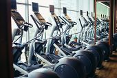 elliptical cross trainer in a row in a gym poster