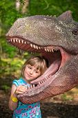 Little girls head in the mouth a dinosaur replica in an amusement park poster