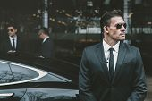 bodyguards going with businessman and reviewing territory near car poster
