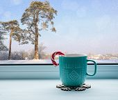 Winter still life - cup with candy cane on windowsill and winter forest landscape outdoors. Winter cozy still life with concept of spending winter time indoors. Winter composition. Winter still life with Christmas mood poster