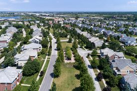 Aerial view of a neighborhood in suburban Chicago with homes on either side of a parkway.