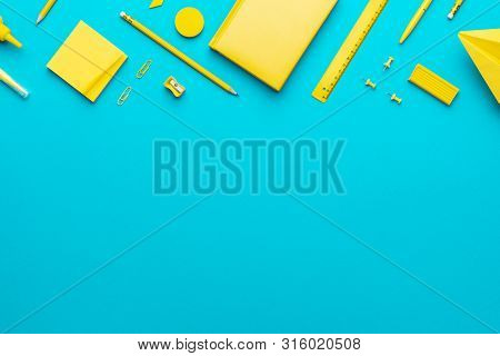 Top View Photo Of Yellow School Stationery On Turquoise Blue Background. School Items In Order With
