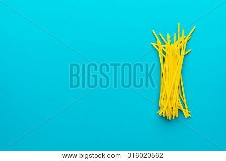 Top View Photo Of Pile Of Yellow Drinking Straws Over Turquoise Blue Background With Copy Space. Fla