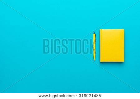 Top View Photo Of Closed Yellow Notebook And Ball-point Pen Over Turquoise Blue Background With Copy