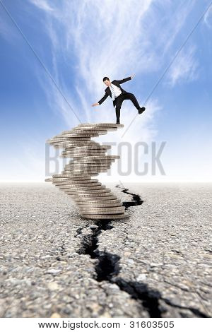 business and Economic crisis concept. cracked road and unstable businessman on the money tower