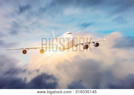 Large Four Engine Jet Passenger Aircraft Flies Through Dense Clouds With Bright Sunshine