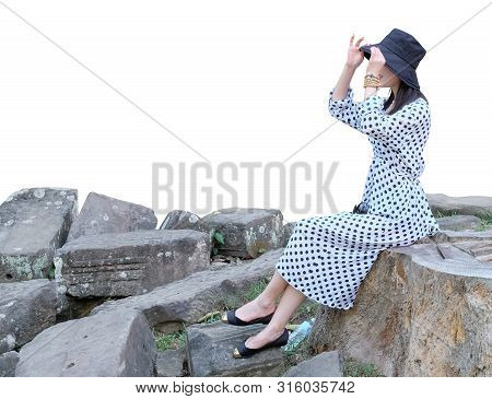 A Young Girl In A White Dress With Polka Dots, Is Sitting On A Stone. Girl In Panama. Isolated. Whit