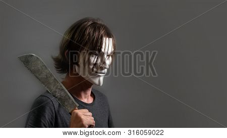 A Man In A Hacker Or Anonymous Mask Holds A Machete On His Shoulder. Halloween Style. Copy Space. Th