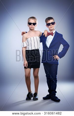 Young schoolchildren posing in a studio. Casual concept for kids. poster