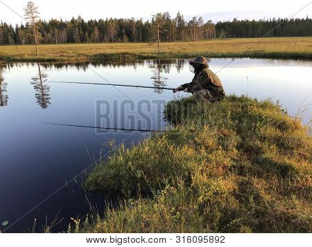 Man Sitting With Fishing-rod At The Shore Of Tranquil Forest Lake