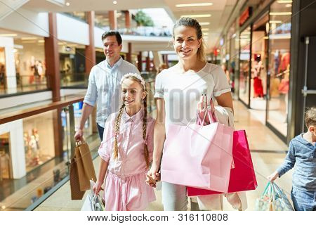 Happy parents and kids shopping in shopping arcade