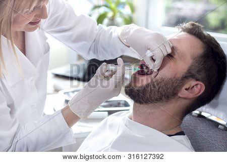 Syringe And Needle With Anesthesia In The Hands Of A Doctor. Injection Into The Upper Gum. The Man W