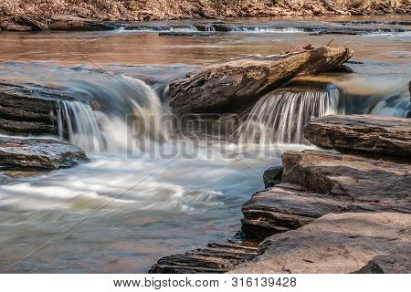 Small Waterfalls Of Water Tumbling Over Rocks Downstream In A River On A Sunny Day In Winter Up Clos