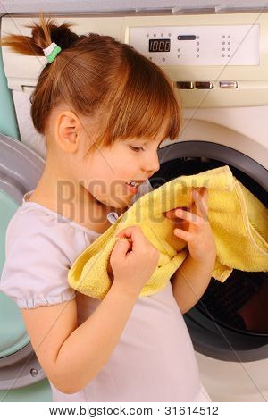 A Little Girl Holding A Towel After Washing