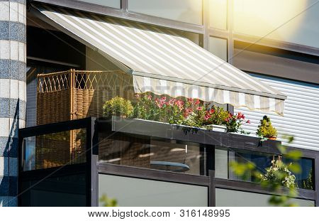 French Balcony With Beautiful Awning And Flowers Covered With Rays Of Sun - Protection During Hot We