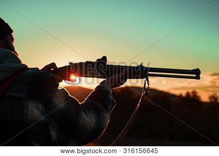 Hunter Man. Barrel Of A Gun. Rifle Hunter Silhouetted In Beautiful Sunset. Hunter With Powerful Rifl