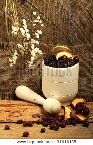 Wooden Mortar And Rose Hips