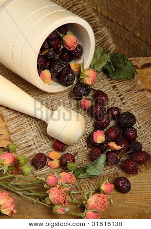 Wooden Mortar And Scattered Rose Hips