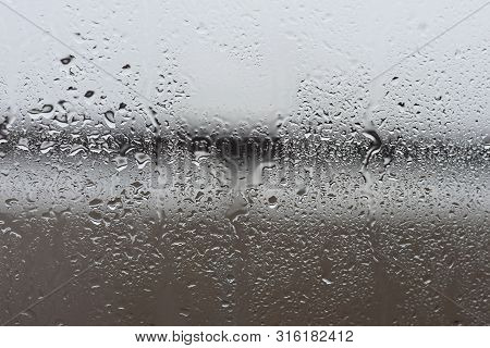 Rain Drops On Window Glass Background At Rainy Day Blurred Outside Sky Cloud Blue Texture