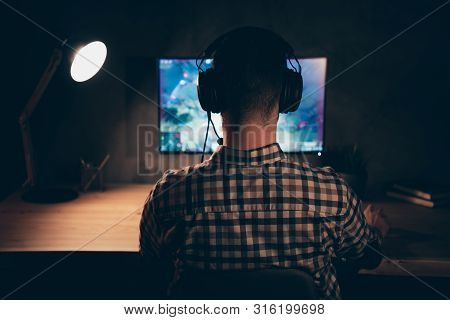 Close up back rear behind view photo he him his guy play videogame battle challenge participation talk teammates headset microphone wear casual plaid checkered shirt internet table house indoors poster
