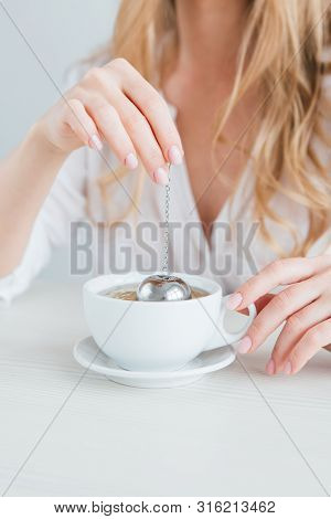 Young Beautiful Girl Brews Tea In A Useful Reusable Metal Strainer