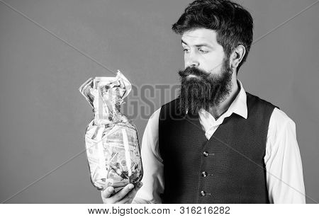 He Respects Money. Bearded Man Keeping Money In Glass Jar. Hipster Holding Jar With American Money.