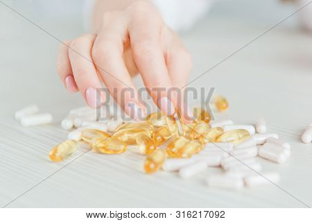 Many Colorful Capsules Of Tablets, Vitamins, Dietary Supplements In Hand On A White Table Close-up