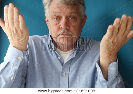 older man with his hands up