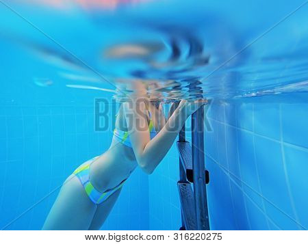 Young Beautiful Girl Is Swimming In The Blue Swimming Pool. Underwater Shoot