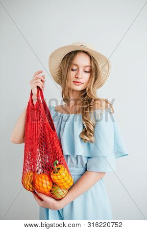 Young Beautiful Girl With Fresh Fruit In A String Bag