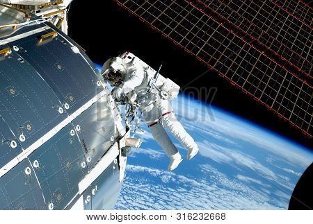 The Astronaut In An Outer Space, At The Iss, Repairs And Makes Experiments. Elements Of This Image W
