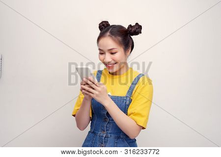 Young Pretty Asian Woman Wearing A Jeans Dungaree And Holding Smartphone