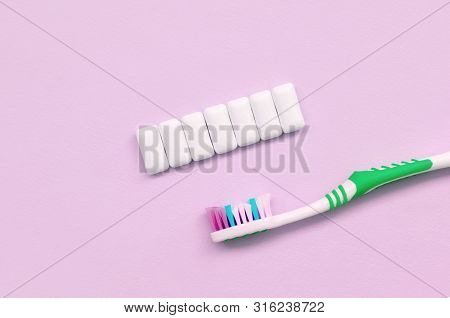 Toothbrush And Chewing Gums Lie On A Pastel Pink Background