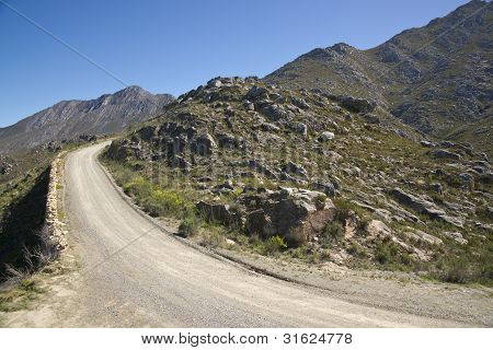 Gravel road heading up to the Swartberg Pass in the Oudtshoorn region of the Western Cape in South Africa. poster