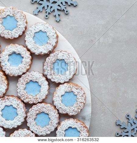 Top View Of Hite And Blue Flower Linzer Cookies On Light Stone Background Decorated With Blue Snowfl