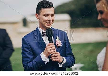 Stylish Groom Pronouncing Vow To His Beautiful Bride During Matrimony. Groom Pronouncing Speech And