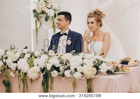 Stylish Bride And Groom Sitting Together At Beautiful Pink Centerpiece Decorated With Flowers At Wed