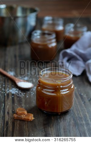 Little Jars Of Salted Caramel Sauce Over A Rustic Table. Selective Focus With Blurred Background.