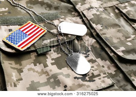 Military Id Tags And Us Army Flag Patch On Camouflage Uniform