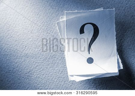 poster of Pile of printed question marks in shaft of light on a textured grey background with copy space in a conceptual image