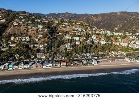 Malibu shoreline and hillside homes aerial near Los Angeles and Santa Monica on Pacific Coast Highway in scenic Southern California.