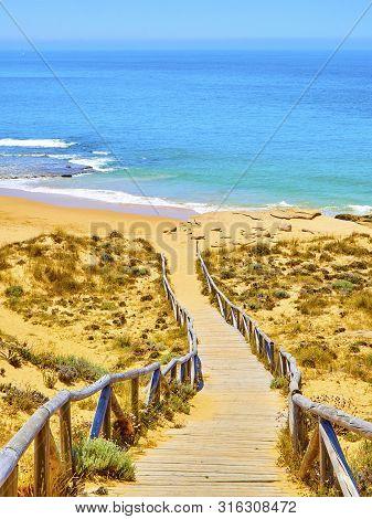 Wooden Boardwalk Going To Faro De Trafalgar Beach, A Broad Beach Of The Cabo De Trafalgar Cape Natur