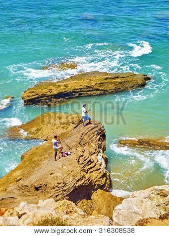 Barbate, Spain - June 26, 2019. Locals Fishing In The Cabo De Trafalgar Cape Natural Park. View From