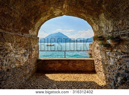 Varenna, Italy. View at lake Como with mountains and sailer yacht from stone arch at seafront.