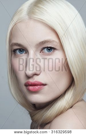 Close-up portrait of young beautiful blonde woman with clean makeup
