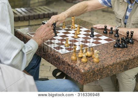 Active Retired People, Old Friends And Free Time, Seniors Having Fun And Playing Chess Game At Park.